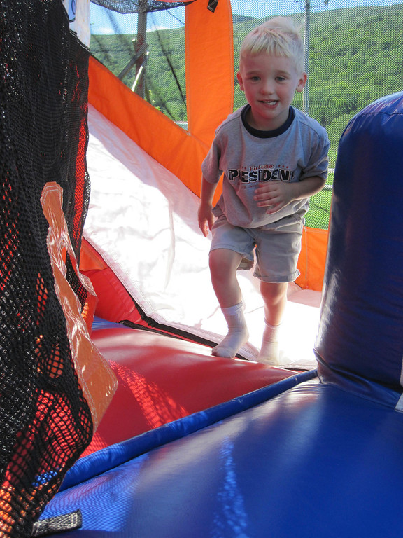 Description of . A youngster trots on a bounce house Sunday during the Adams Youth Center annual family fun day held at The Range in North Adams. Jenn Smith/Berkshire Eagle Staff Sunday, Aug. 11, 2013