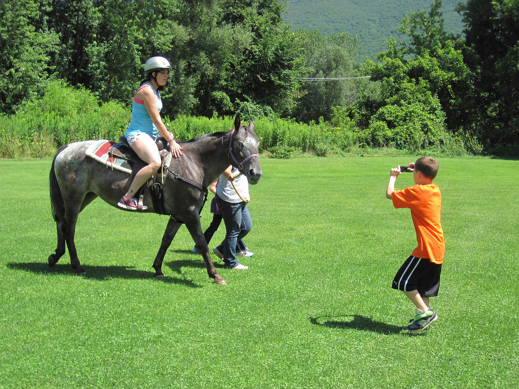 Description of . Zack Lillie, 9, of Adams plays paparazzi, taking photos of his mother, Paula Cadrett, while she takes a horse ride during the Adams Youth Center family fun day held Sunday at The Range in North Adams. Jenn Smith/Berkshire Eagle Staff Sunday, Aug. 11, 2013