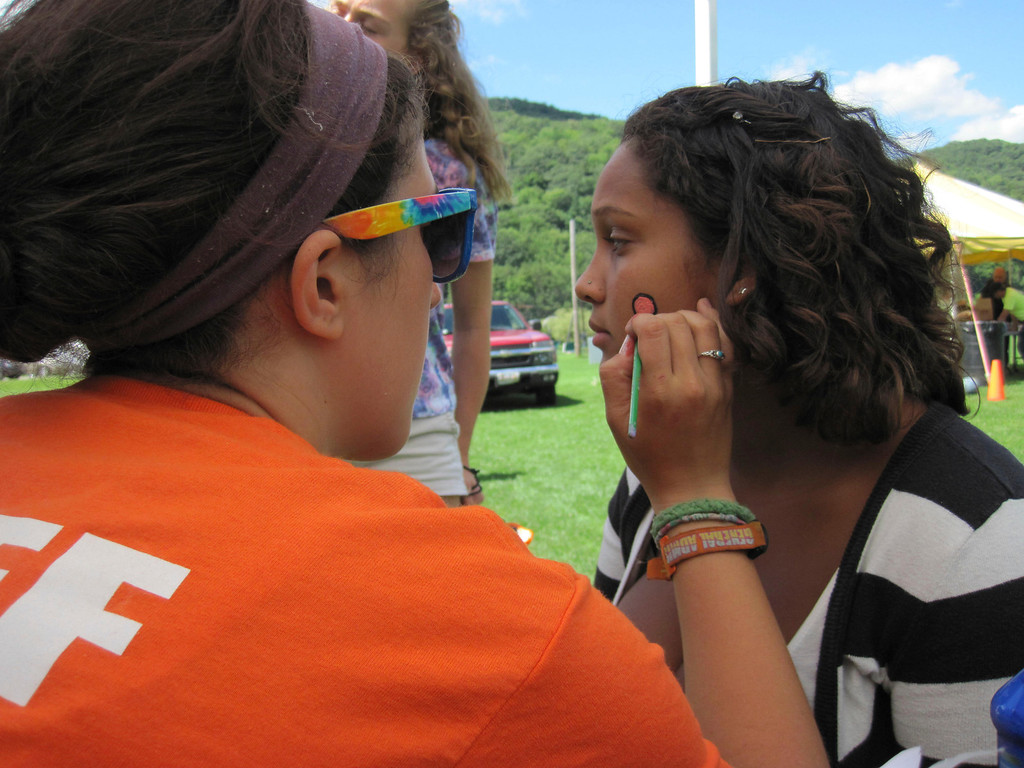 Description of . Adams Youth Center camp counselor Jessica Sweeney, 24, (left) paints an American Indian style motif design on the cheek of 17-year-old Kuwanna Bobbitt during the center's annual family fun day held Sunday at The Range in North Adams. Jenn Smith/Berkshire Eagle Staff Sunday, Aug. 11, 2013