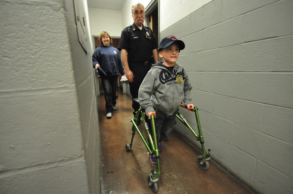 Description of . WIth his mother Dr. Heather Blake and North Adams Police Officer Fran Maruco in tow, Brayton Elementary School first grader Zach Hillard, 7, walks through the halls of the North Adams Police Department during a tour on Tuesday, April, 29, 2014. Gillian Jones / Berkshire Eagle Staff / photos.berkshireeagle.com