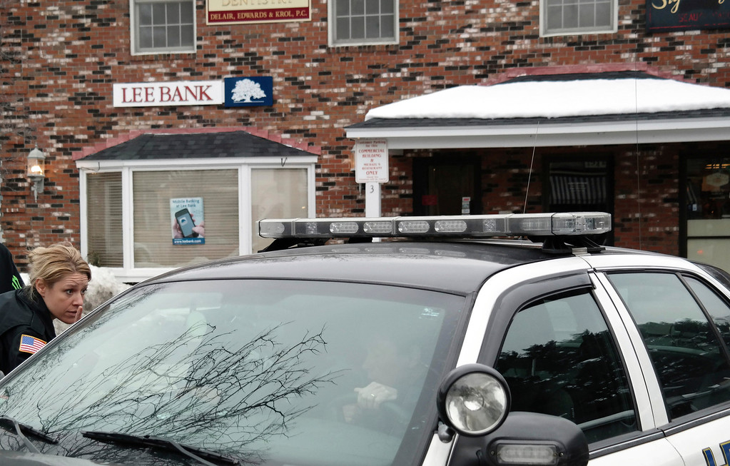 Description of . Stockbridge police officer Heidi Teusch talks with another officer in a squad car at the scene of the Lee Bank branch on Elm Street in Stockbridge. Police were investigating an alleged robbery that took place there Monday afternoon. Ben Garver/Berkshire Eagle Staff Monday, March 10, 2014