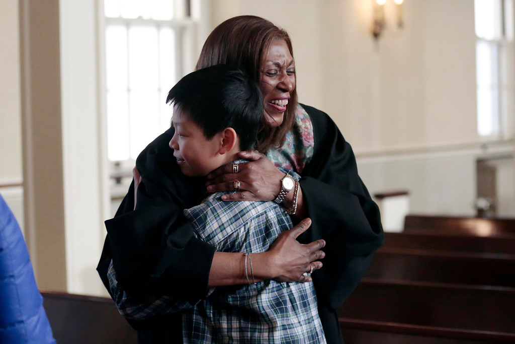 Description of . The Rev. Sheila Sholes-Ross, the new pastor at First Baptist Church in Pittsfield, greets Chenyang Lin, 13, after Sunday service. Sunday, January 26, 2014. (Stephanie Zollshan | Berkshire Eagle Staff)