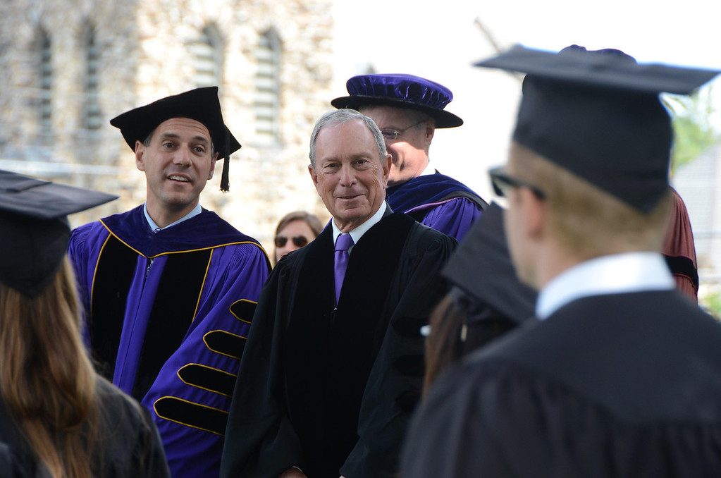 Description of . Williams College President Adam Falk and Former NYC Mayor Michael Bloomberg watch as student march in a procession from Chapin Hall to graduation exercises at the college's 225th commencement on Sunday, June, 8, 2014. Gillian Jones / Berkshire Eagle Staff / photos.berkshireeagle.com