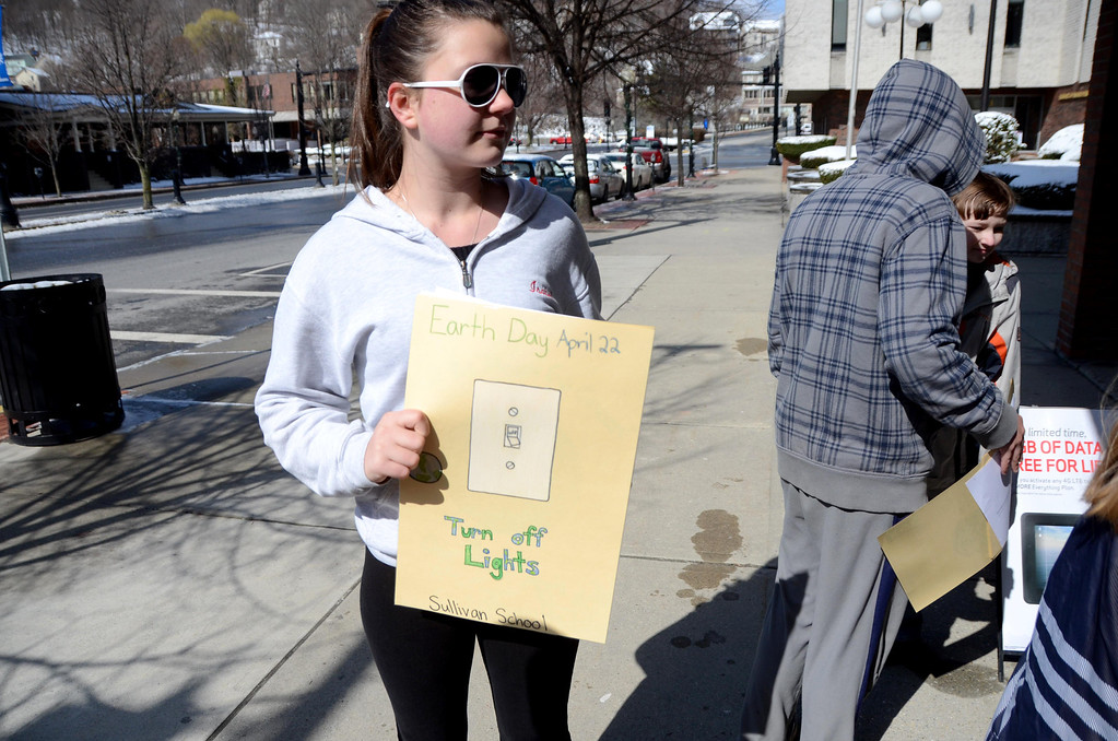 Description of . Sullivan School student Isabel Lescarbeau, 12, holds up an Earth Day poster that she made in Jim Holmes' sixth grade class. Students gave them to local businesses to display in their storefronts in downtown North Adams on Wednesday, April, 16, 2014. Gillian Jones / Berkshire Eagle Staff / photos.berkshireeagle.com