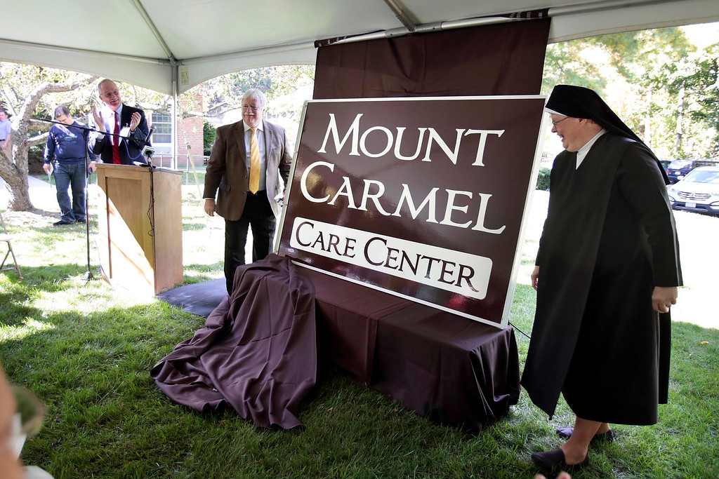 Description of . Mother Mark of the Carmelite Sisters and Christopher McLaughlin unveil a new official building sign at a press conference announcing the sale of the Providence Care Center from the Sisters of Providence Health System to the Carmelite Sisters at the facility in Lenox. Monday, September 30, 2013. Stephanie Zollshan/Berkshire Eagle Staff.