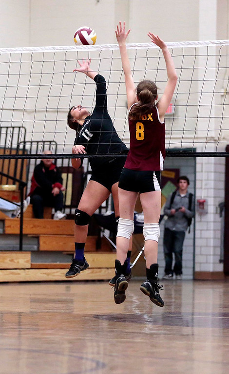 Description of . Pittsfield's Sienna Carpenter jumps up to spike the ball as Lenox's Lizzy Barry tries to block it during a volleyball game at Lenox Memorial High School. Monday, September 23, 2013. Stephanie Zollshan/Berkshire Eagle Staff.