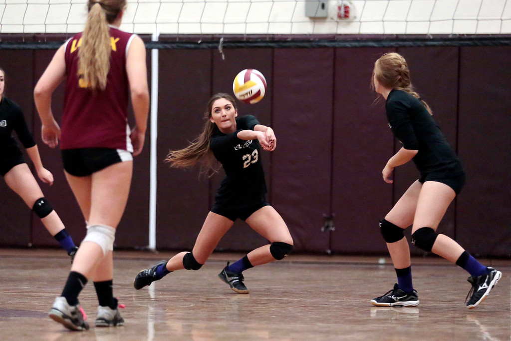 Description of . Pittsfield's Paige Hamilton dives for the ball during a volleyball game at Lenox Memorial High School. Monday, September 23, 2013. Stephanie Zollshan/Berkshire Eagle Staff.
