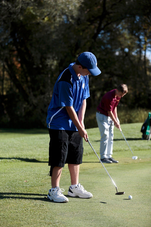 Description of . Wahconah's Thomas Gonzales putts as Lenox's Noah Hunter, back, lines up his putt during a golf match at Wahconah Country Club in Dalton. Monday, September 30, 2013. Stephanie Zollshan/Berkshire Eagle Staff.