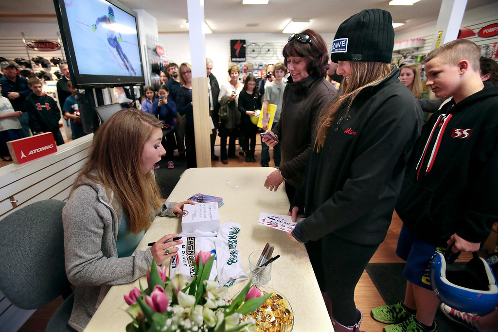 Description of . The Bartlett family gives a box of cider donuts from their farm, Bartlett's Orchards, to Sochi Olympic gold medalist Mikaela Shiffrin during her visit to Plaine's Bike, Ski and Snowboard to meet fans and sign autographs. Wednesday, April 9, 2014. Stephanie Zollshan / Berkshire Eagle Staff / photos.berkshireeagle.com