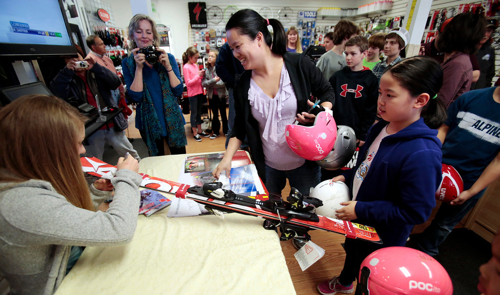 Description of . Sochi Olympic gold medalist Mikaela Shiffrin signs a pair of skis for Abigail Eng, 9, right, during her visit to Plaine's Bike, Ski and Snowboard to meet fans and sign autographs. Wednesday, April 9, 2014. Stephanie Zollshan / Berkshire Eagle Staff / photos.berkshireeagle.com