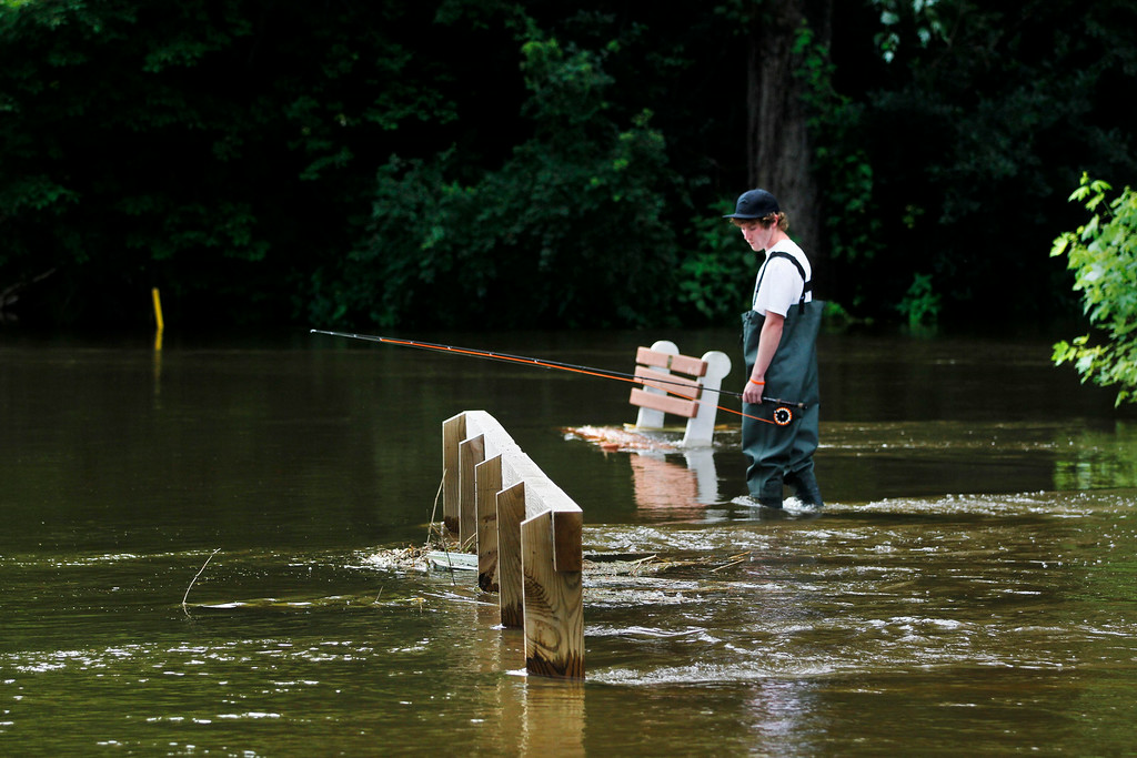 Description of . A fisherman looks for a good spot to fly fish by the submerged fifteeth tee at the Stockbridge Golf Club. Much of the course is under water due to the recent heavy rains in the area. Tuesday, July 29, 2014. Stephanie Zollshan / Berkshire Eagle Staff / photos.berkshireeagle.com