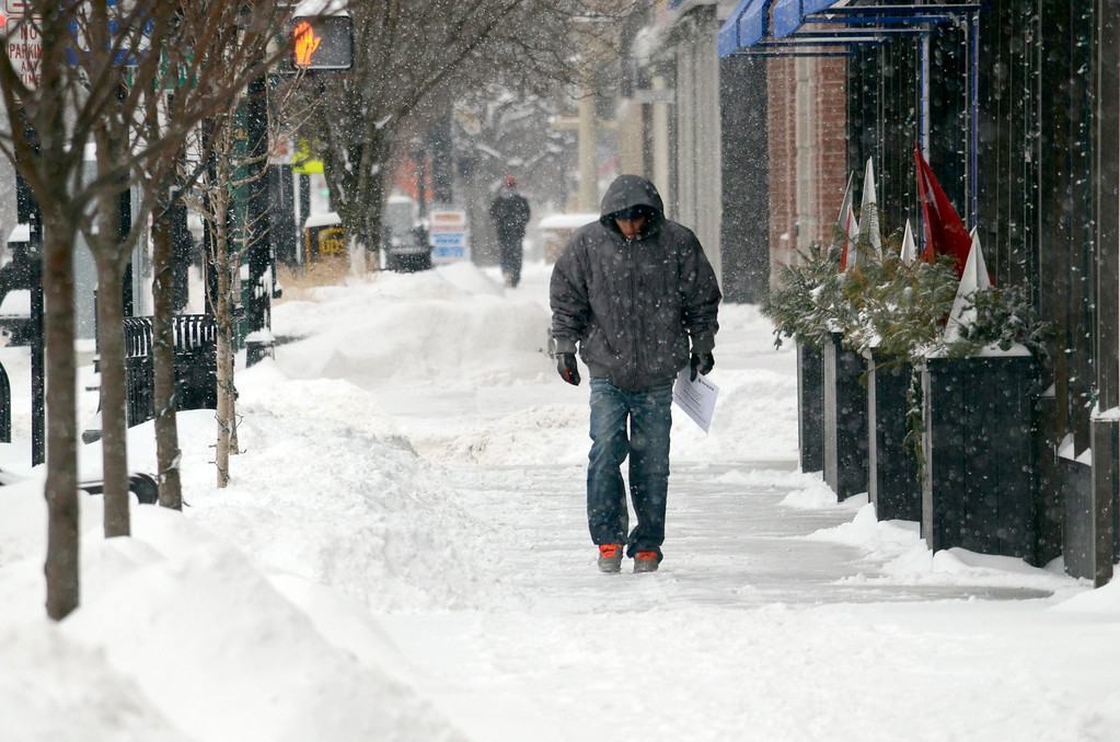 Description of . A man walks on North Street in Pittsfield among piles of freshly fallen snow, Wednesday Feb 5, 2014.  Photo by Ben Garver / Berkshire Eagle Staff