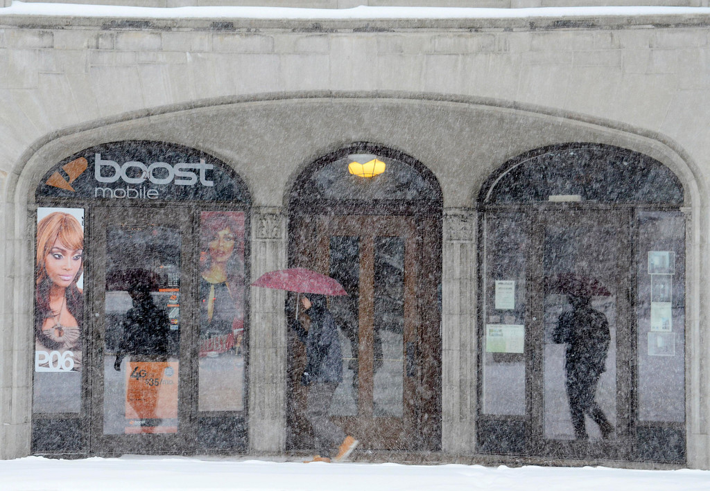 Description of . A pedestrian passes a North Street Storefront in Pittsfield during heavy morning snow, Wednesday Feb. 5, 2014.  Photo By Ben Garver / Berkshire Eagle Staff