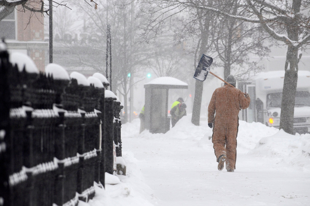 Description of . A man walks South on Noprth Street near St. Josephs Church in Pittsfield with a shovel in hand, Wednesday Feb 5, 2014.  Photo by Ben Garver / Berkshire Eagle Staff
