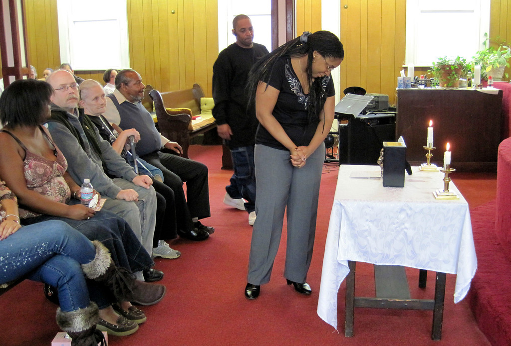 Description of . Nadine Turner looks at a small tribute to the memory of David Glasser in front of the altar at Price Memorial Church in Pittsfield.  Mon Nov 28, 2011 (GARVER)