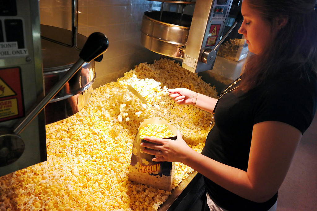 . Brianna Flynn prepares popcorn at the Beacon Cinema. The Beacon Cinema in Pittsfield does not allow outside food, and is implementing a more customer-friendly approach to enforcing the rule. Monday May 12, 2014.  Ben Garver / Berkshire Eagle Staff / photos.berkshireeagle.com