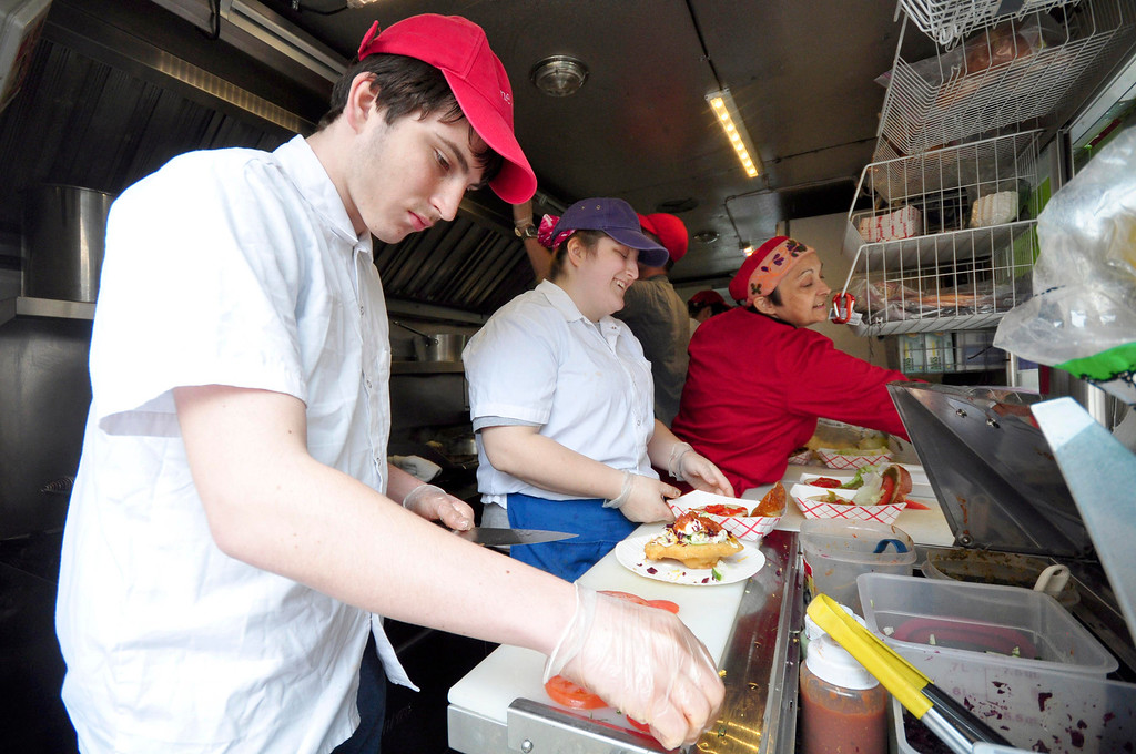 . From left, Stephen Herron, 16, Allyssa Herron and Chef Aurora Marin prepare food in the food truck of Aurora\'s Gypsy Cafe during the community event in Palace Park to benefit Moments House in Pittsfield on Sunday, May, 4, 2014. Gillian Jones / Berkshire Eagle Staff / photos.berkshireeagle.com
