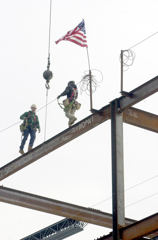 """. After securing the beam, workers from Columbia Development Group walk along the final steel beam that was lowered onto what is to become the new Ambulatory Care Center at North Adams Regional Hospital, during the \""""topping out\"""" ceremony held yesterday morning. Feb. 26, 2002.Caroline Bonnivier Snyder/North Adams Transcript"""