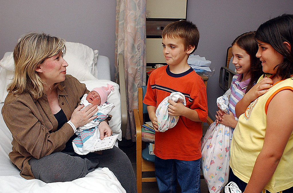. As part of a community service learning project at Brayton School, Claire Angeli\'s fourth graders made book bags for new moms with items to promote early literacy. New mom Susan Bendavid and her daughter Caroline Grace receive a bag from T.J. Skiffington, 9, Ashleigh Rennell, 8, and Ashley Mirante, 9 at North Adams Regional Hospital on Wednesday June 19. June, 22, 2002. File photo by Gillian Jones