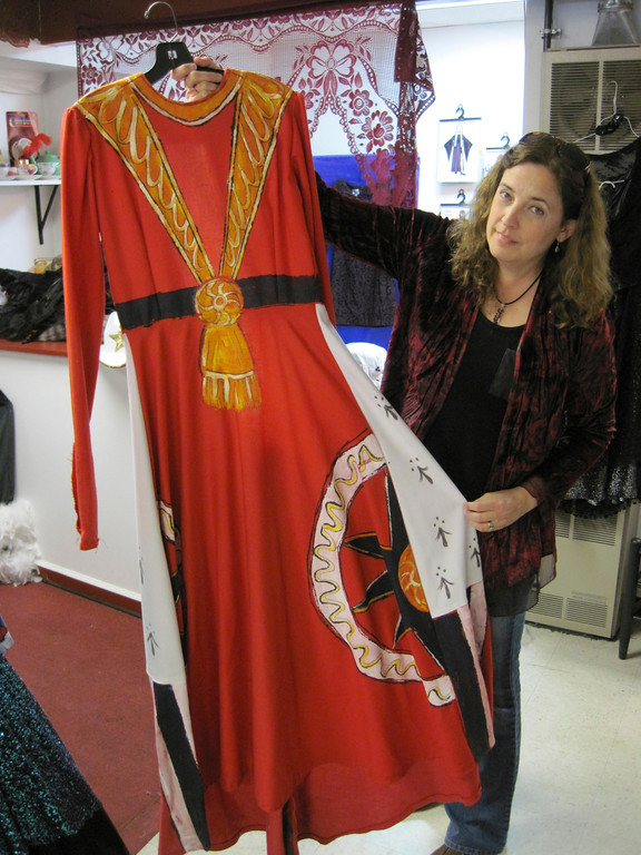 . Berkshire Costume Company owner Kara Demler shows how a long, plain red dress was painted to look like a royal garment. Jenn Smith/Berkshire Eagle Staff Oct. 18, 2013