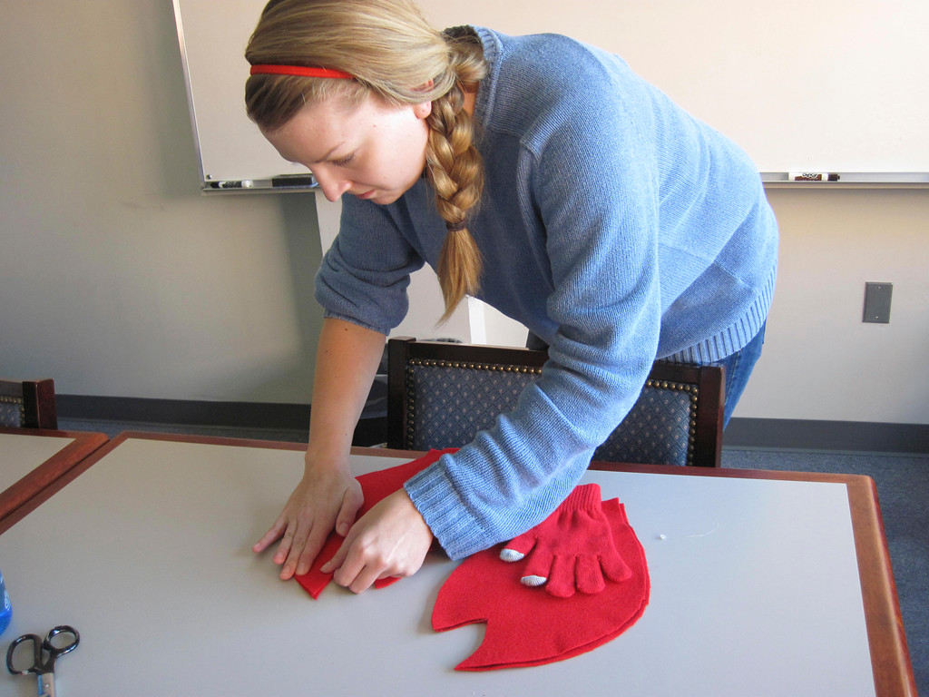 . Eagle online editor Laura Lofgren hot glues hand-traced, hand-cut red felt lobster claw shapes over a red glove to creates a DIY lobster claw, as used in a homemade \'Lobster-in-a-Pot\' costume worn by Eagle features editor Lindsey Hollenbaugh. Jenn Smith/Berkshire Eagle Staff Oct. 18, 2013