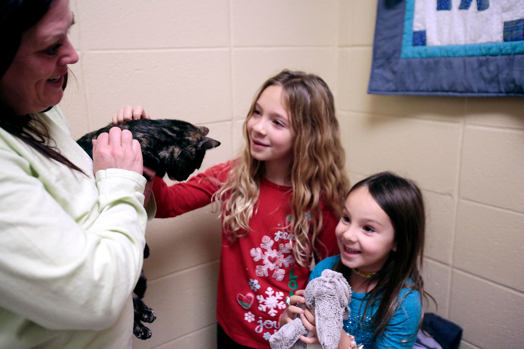 . Colleen McGrath hands over Skittles to Alex, 8, left, and Jordan Sotek, 5, her new adoptive family, at the Berkshire Humane Society in Pittsfield. Sunday, December 29, 2013. (Stephanie Zollshan | Berkshire Eagle Staff)