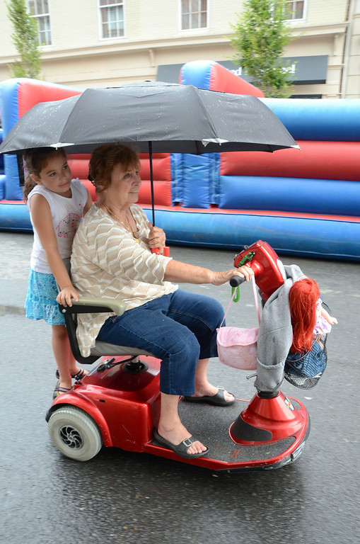. With an umbrella to keep them dry, Chantal Evans, 6, rides on the back of Barbara MacWhinnie\'s scooter at the Pittsfield Ethnic Fair and Classic Car Show on North Street in Pittsfield on Sunday, July, 27, 2014. MacWhinnie is Chantal\'s great aunt. Gillian Jones / Berkshire Eagle Staff / photos.berkshireeagle.com