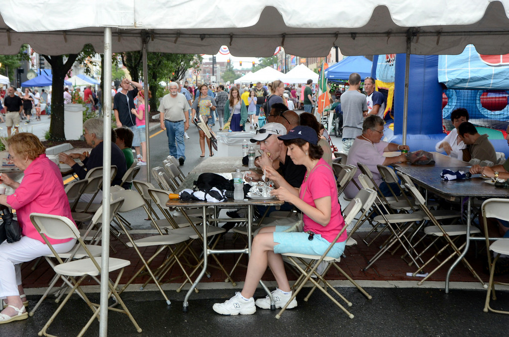 . People enjoy food under a tent at the Pittsfield Ethnic Fair and Classic Car Show on North Street in Pittsfield on Sunday, July, 27, 2014. Gillian Jones / Berkshire Eagle Staff / photos.berkshireeagle.com