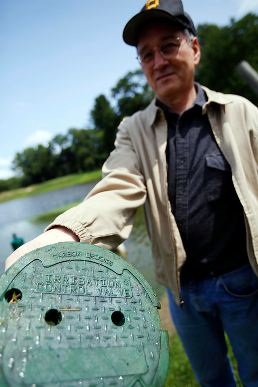 . John Mackie holds an irrigation control valve cover that he found floating in the water near the second tee at Stockbridge Golf Club. Much of the course is under water due to the recent heavy rains in the area. Tuesday, July 29, 2014. Stephanie Zollshan / Berkshire Eagle Staff / photos.berkshireeagle.com