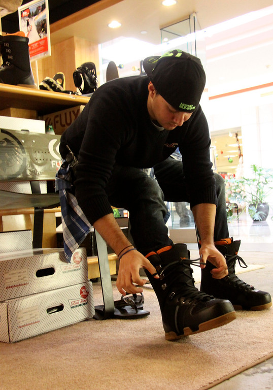 . Dave Heming of Pittsfield tries on a pair of snowboard boots while shopping at Gilly\'s Snowboard shop. Gilly\'s is a new store at the Berkshire Mall and is one of many that has been opening for the holiday season. Gilly\'s offers snowboards, clothing and gear. November 5th 2013 Holly Pelczynski/Berkshire Eagle Staff