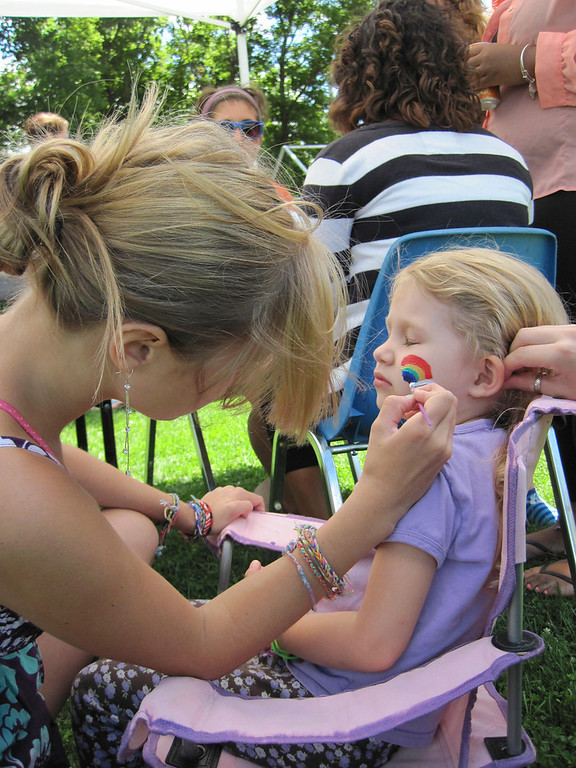 . Marissa Roberts, 13, a volunteer and member of the Adams Youth Center, paints a rainbow on the cheek of 4-year-old Madeline Rogers of Adams, during the center\'s family fun day held Sunday at The Range in North Adams. Jenn Smith/Berkshire Eagle Staff Sunday, Aug. 11, 2013