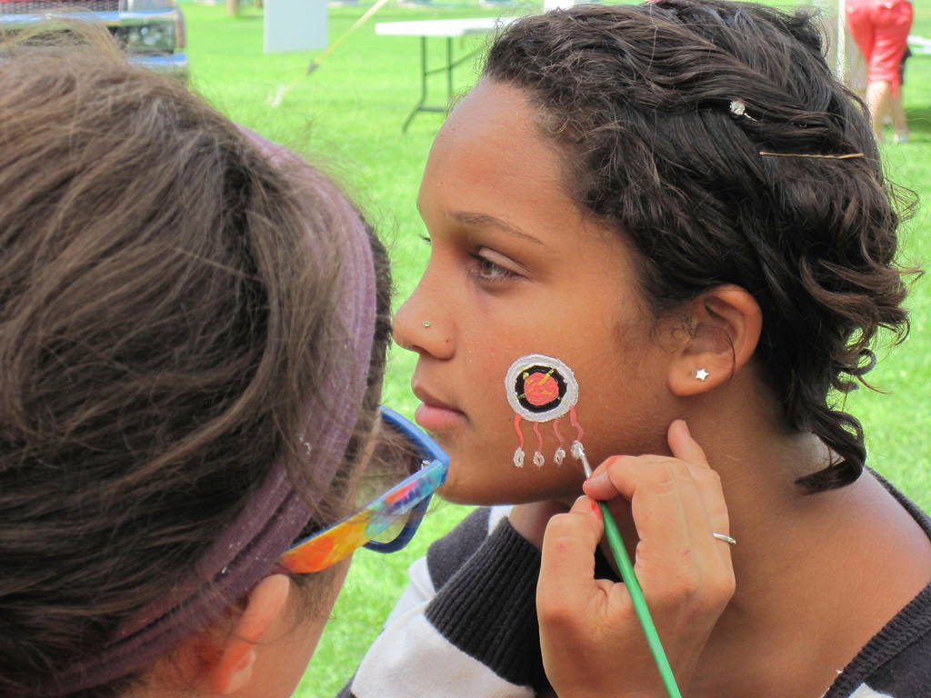 . Adams Youth Center camp counselor Jessica Sweeney, 24, (left) paints a Native American style motif design on the cheek of 17-year-old Kuwanna Bobbitt during the center\'s annual family fun day held Sunday at The Range in North Adams. Jenn Smith/Berkshire Eagle Staff Sunday, Aug. 11, 2013
