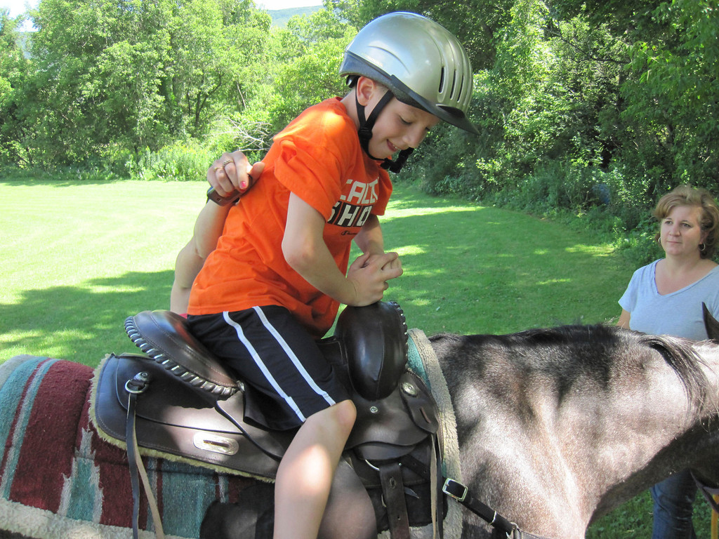. Paula Cadrett (hand) helps her son Zack Lillie, 9, settle in the saddle worn by Stella, a 14-year-old Appaloosa horse, as owner Melanie Richard looks on. The horse rides were offered as part of the Adams Youth Center family fun day and mini golf tournament on Sunday. Jenn Smith/Berkshire Eagle Staff Sunday, Aug. 11, 2013