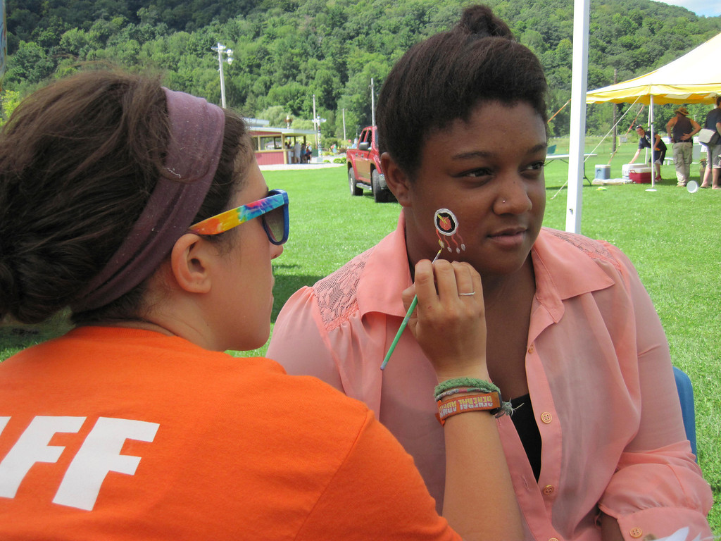 . Adams Youth Center camp counselor Jessica Sweeney, 24, (left) paints an American Indian style motif design on the cheek of 15-year-old Raja King during the center\'s annual family fun day held Sunday at The Range in North Adams. Jenn Smith/Berkshire Eagle Staff Sunday, Aug. 11, 2013