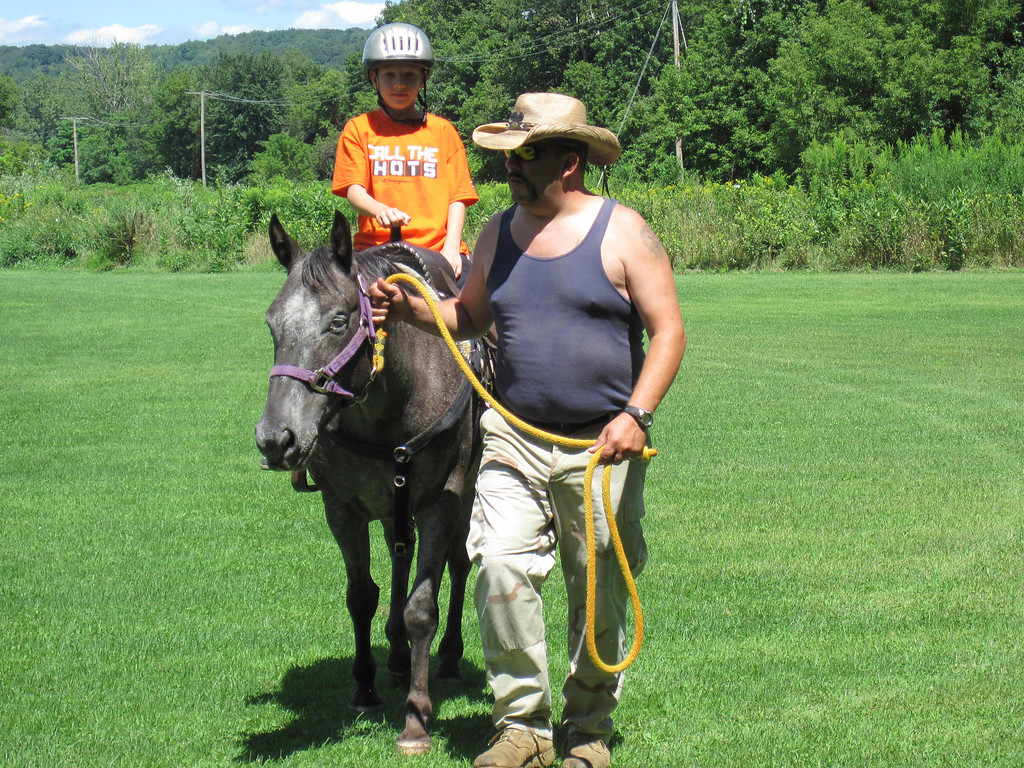 . Nine-year-old Zack Lillie of Adams takes a ride on Stella the Appaloosa, led by owner Rob Matte. Horse rides were offered as part of the Adams Youth Center\'s annual family fun day held Sunday at The Range in North Adams. Jenn Smith/Berkshire Eagle Staff Sunday, Aug. 11, 2013