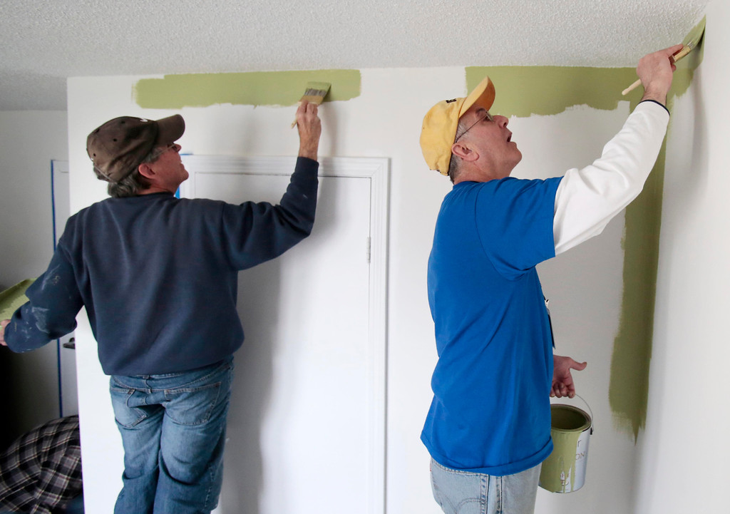 . Mayor Daniel Bianchi, right, joins AmeriCorps VISTA and John Keegan of the Retired Senior Volunteer Program (RSVP) in painting a room at the Central Berkshire Habitat for Humanity office in Pittsfield as he participates in the Mayors Day of Recognition for National Service. Tuesday, April 1, 2014. Stephanie Zollshan / Berkshire Eagle Staff / photos.berkshireeagle.com