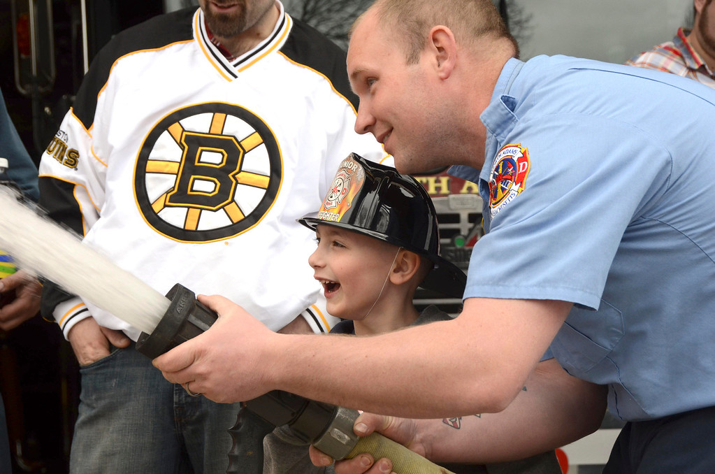 . Brayton Elementary School first grader Zach Hillard, 7, holds the fire hose with the help of North Adams Firefighter John Lancto on Tuesday, April, 29, 2014. Gillian Jones / Berkshire Eagle Staff / photos.berkshireeagle.com