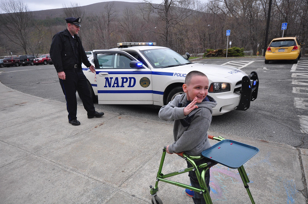 . Brayton Elementary School first grader Zach Hillard, 7, who has cerebral palsy, had his wish come true on Tuesday, April, 29, 2014. Hillard, who is undergoing major surgery in June, got the chance to spend the morning with North Adams Police Officer Mark Bailey, ride in a police cruiser, arrest his mother, meet the Mayor, tour the police and fire departments and ride in a North Adams Fire Department truck. Zach waves goodbye to his classmates as he begins his adventure. Gillian Jones / Berkshire Eagle Staff / photos.berkshireeagle.com