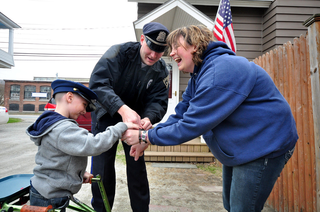 . Brayton Elementary School first grader Zach Hillard, 7, with the help of North Adams Police Officer Mark Bailey, arrests his mother, Dr. Heather Blake, from their State Road home in North Adams on Tuesday, April, 29, 2014. Gillian Jones / Berkshire Eagle Staff / photos.berkshireeagle.com