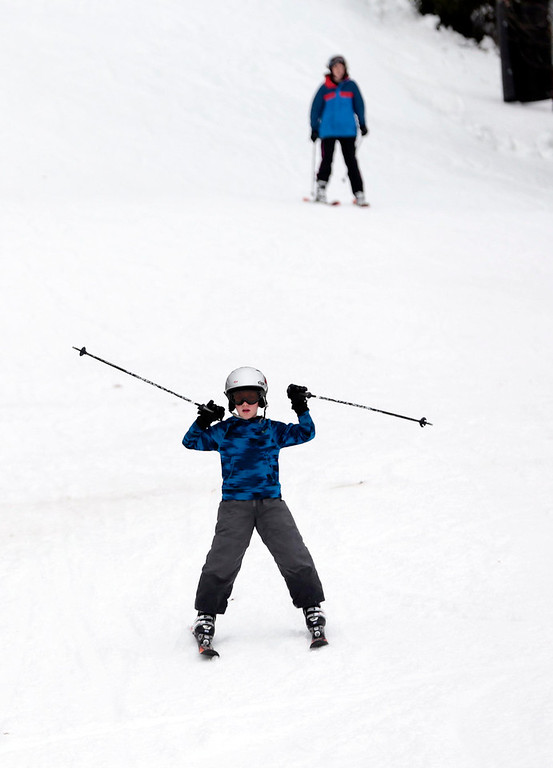 . Gregory Effman, 8, skis toward the lifts with his mother, Ingrid, behind him. Though grass still covers most of the mountain, ski and snowboard enthusiasts take to the slopes on opening weekend of Jiminy Peak in Hancock. Sunday, November 17, 2013. (Stephanie Zollshan | Berkshire Eagle Staff)