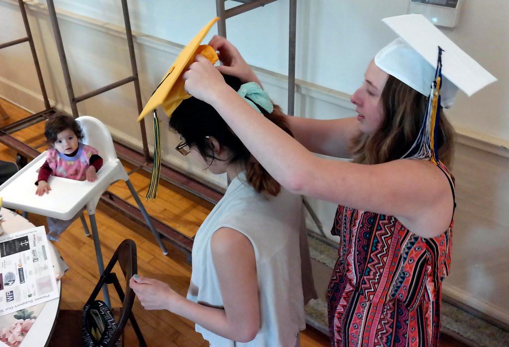 . Baby hailey Van Rumund watches Krystal Ferrari put a graduation cap on her mother Ashley Reyes at the Teen Parent Program commencement in Pittsfield. Friday June 6, 2014.  Ben Garver / Berkshire Eagle Staff / photos.berkshireeagle.com