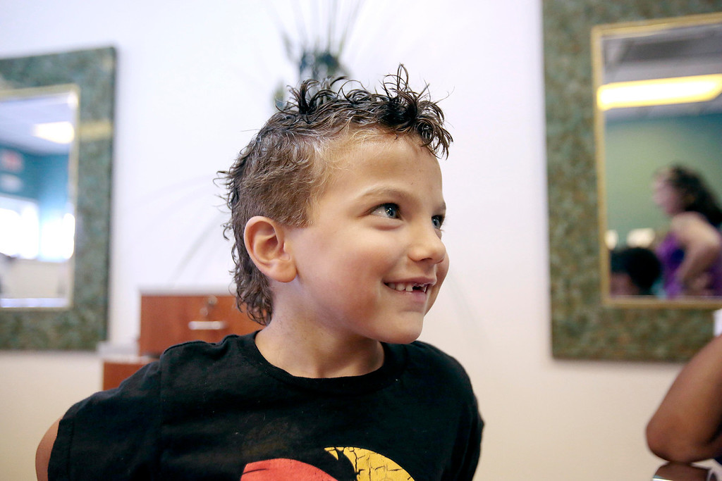 . Kingston DeJesus, 5, smiles at his family after getting his first haircut, which took off over 15 inches of hair, at Split Ends Hair Salon in Pittsfield. Saturday, August 3, 2013. Stephanie Zollshan/Berkshire Eagle Staff.