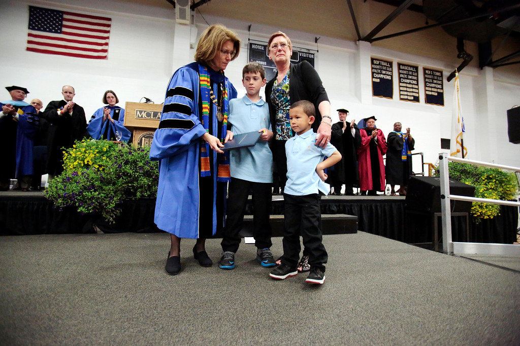 . On behalf of their mother who passed away on May 10, Rebecca Haskell\'s sons accept her diploma on her behalf from school president Mary Grant during the MCLA commencement ceremony in North Adams. Saturday, May 17, 2014.