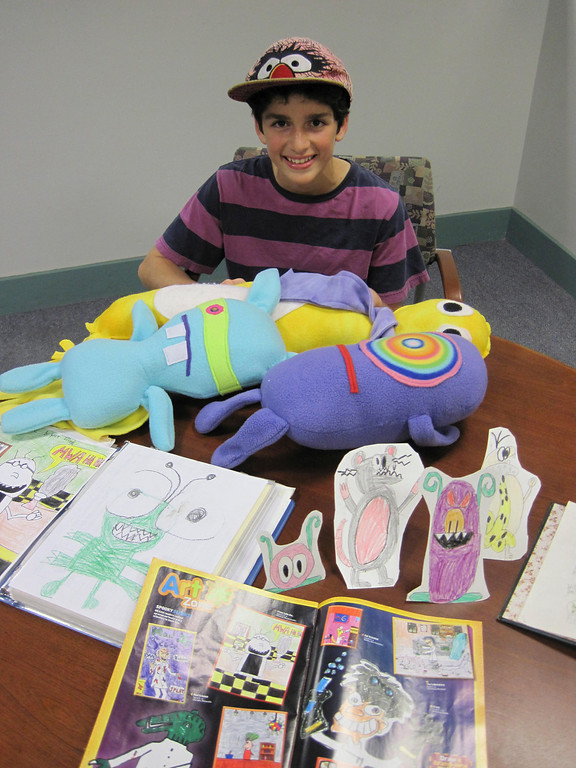 . Spencer Villinski, 11, of Pittsfield, poses with his character creations, from hand drawings, paper dolls and plush monsters, as well as the drawing he has published in this month\'s National Geographic Kids magazine. Jenn Smith/Berkshire Eagle Staff Monday, Oct. 21, 2013