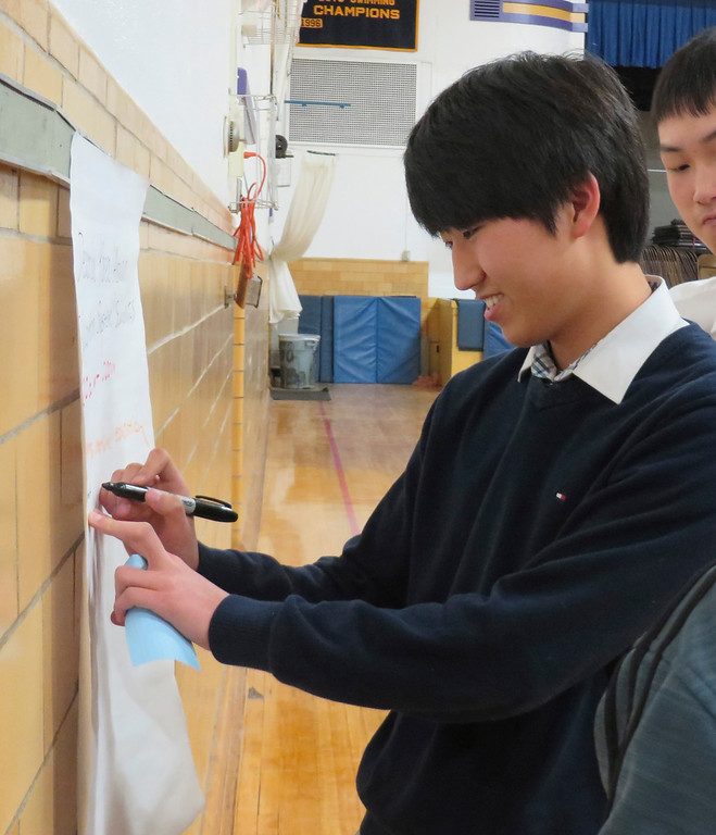 . St. Joseph Central High School exchange student Keunuk Jeong, 17, makes a list of what the educational system is like in South Korea during a cultural workshop presented on North and South Korea by international educational consultant Christine Canning-Wilson. Jenn Smith/Berkshire Eagle Staff Friday, March 16, 2014