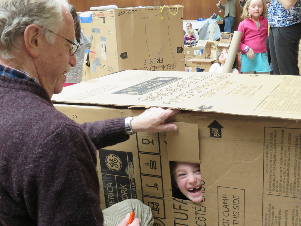 . Stella Nadelberg of Lexington, Mass. peaks out of window made by her grandfather, architect Peter Shaffer of Tyringham and Boston, in a cardboard fort they built together at the Ten Days of Play exhibit at the Berkshire Museum in Pittsfield. Jenn Smith/Berkshire Eagle Staff Monday, Feb. 17, 2014