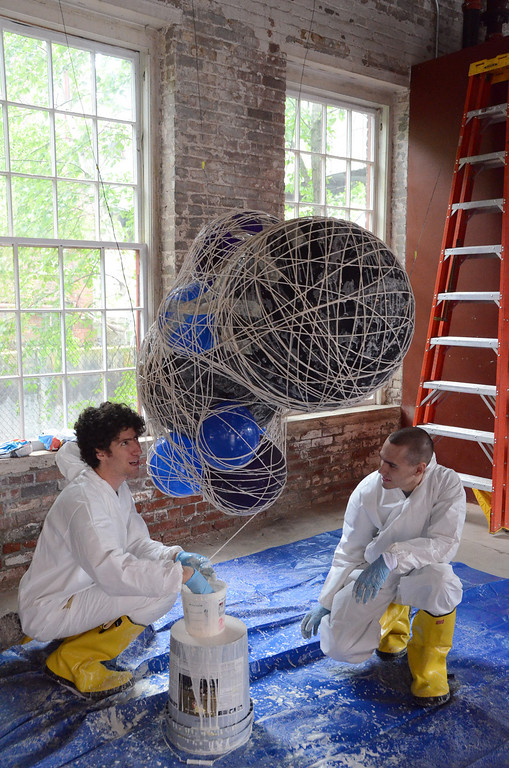 . Gillian Jones/North Adams Transcript Jackson Kleiser, right, assists Jeremy Roth, who does lighting visual production and design, with making string lamps or \'clouds\' that will hang over the stage during the Solid Sound weekend at Mass MoCA starting on Friday.