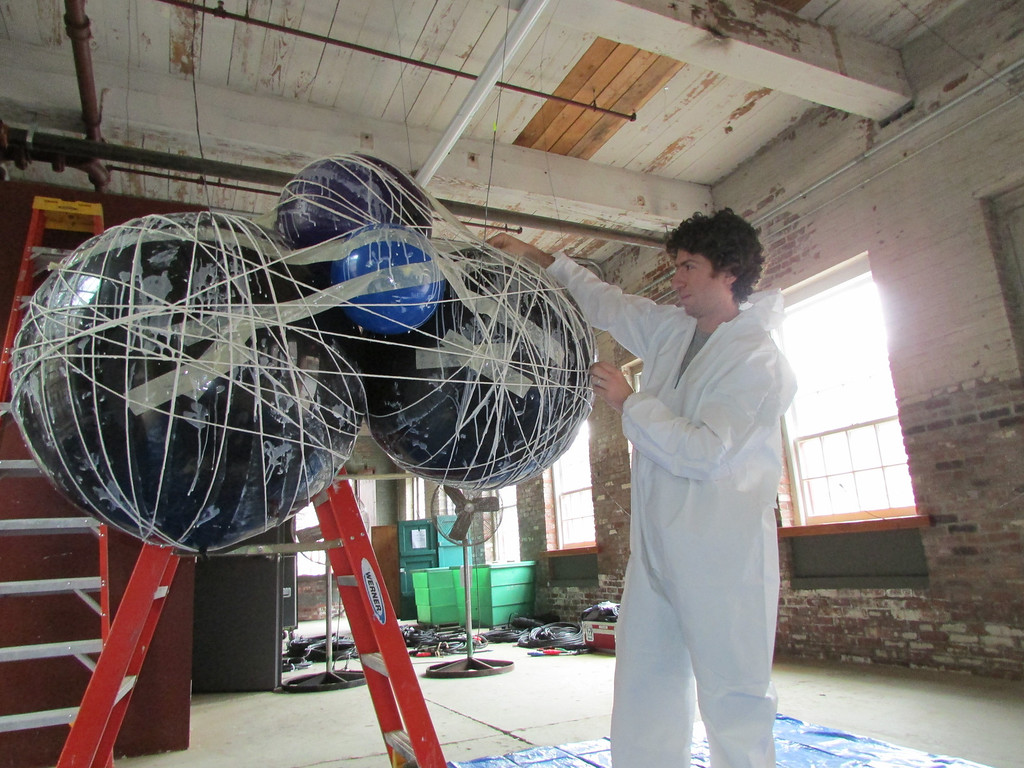 """. On Tuesday, Wilco\'s Lighting and Visual Production Designer Jeremy Roth works on a \""""string cloud\"""" that will hold lights during Wilco\'s concerts at Solid Sound Festival 2013. The string cloud lights will be exclusive to the festival. (Jennifer Huberdeau/North Adams Transcript)"""