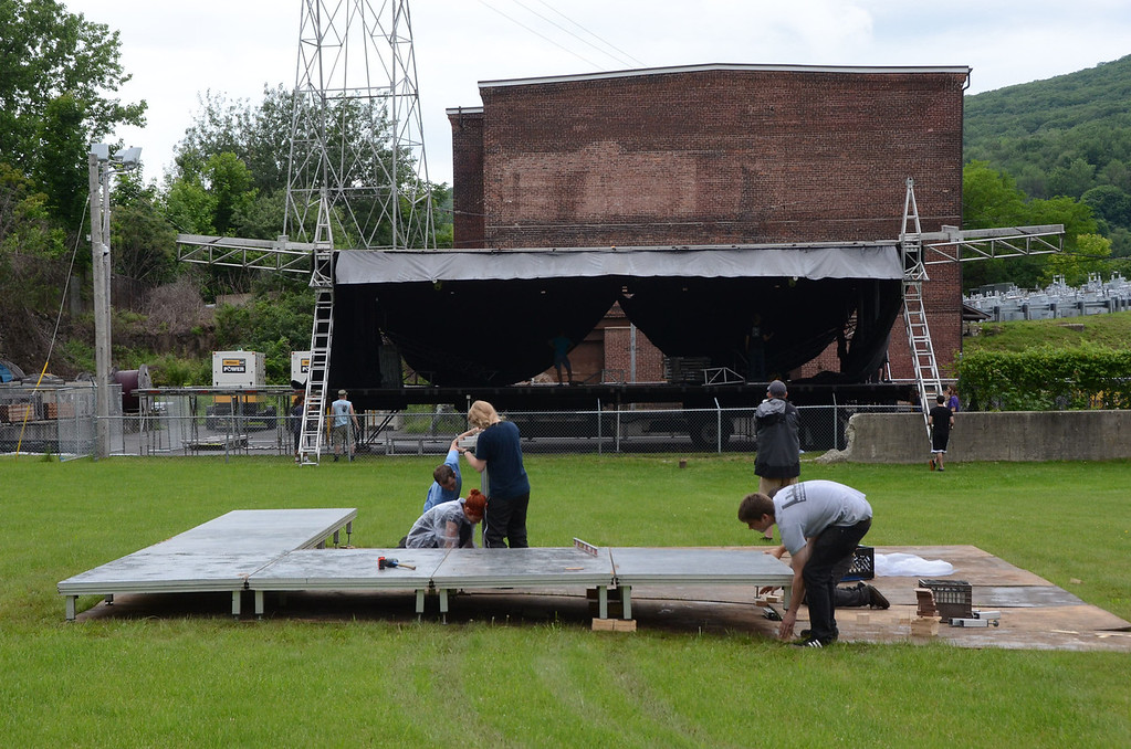 . Gillian Jones/North Adams Transcript Workers put together the \'front of house,\' or control station for audio and lighting, in the foreground, while in the background other workers assemble the outdoor stage at Joe\'s Field for Solid Sound this weekend at Mass MoCA.