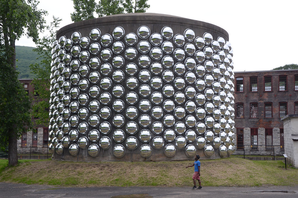 . Gillian Jones/North Adams Transcript A man walks past \'Can\'t Hear You\' (Fat Totem) an installation of acrylic dome safety mirrors mounted on a former fire control tank in Joe\'s Field at Mass MoCA by artist Marko Remec. The mirrors are secured with steel aircraft cable, as well as assorted steel and aluminum hardware.